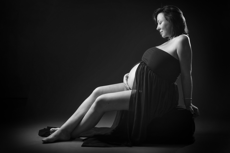 Portrait en noir et blanc de femme enceinte assise pour Lorie Diaz photographe