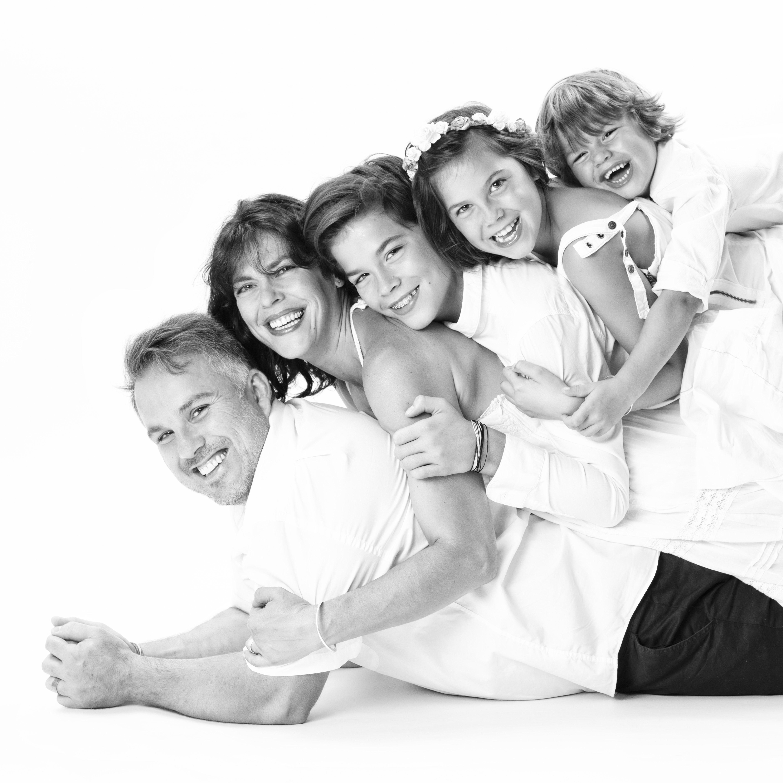 Photo de famille en studio en noir et blanc d'une famille avec un couple et leurs enfants allongés sur le dos les uns des autres pour Lorie Diaz photographe