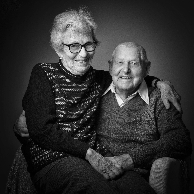 Portrait en noir et blanc en studio d'un couple sur fond gris pour Lorie Diaz photographe