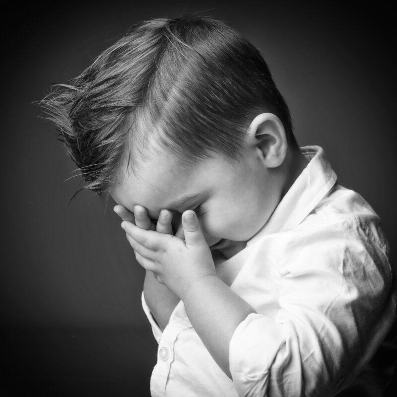 Portrait en studio en noir et blanc sur fond noir d'un petit garçon pour Lorie Diaz