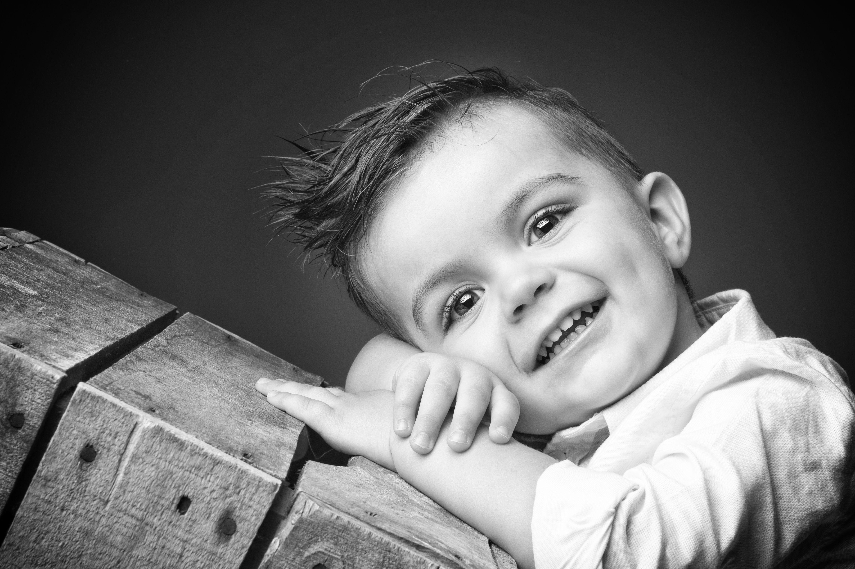 Portrait en studio en noir et blanc sur fond noir d'un petit garçon de face sur une caisse en bois pour Lorie Diaz