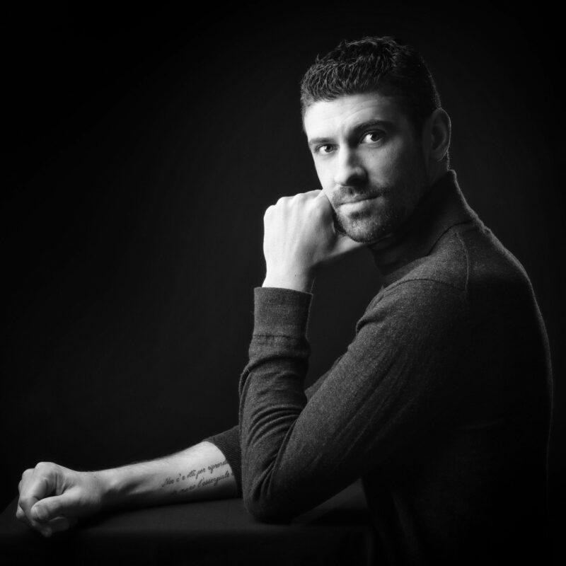 Portrait en studio en noir et blanc sur fond noir d'un jeune homme pour Lorie Diaz