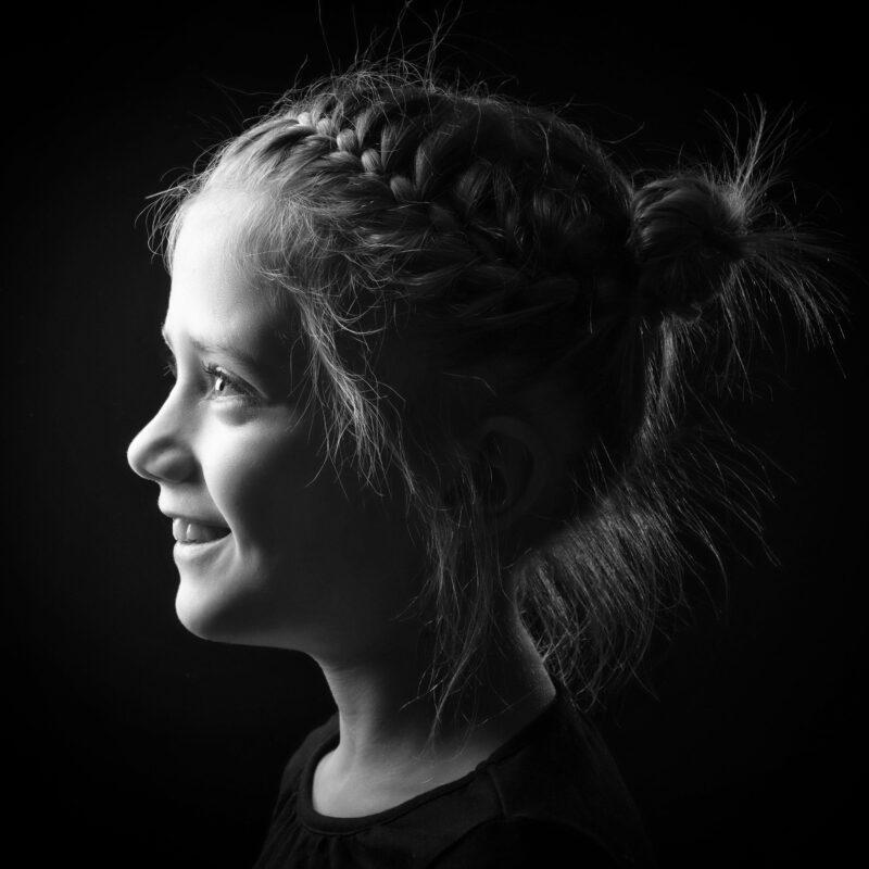 Portrait en studio en noir et blanc sur fond noir d'une jeune fille de profil pour Lorie Diaz