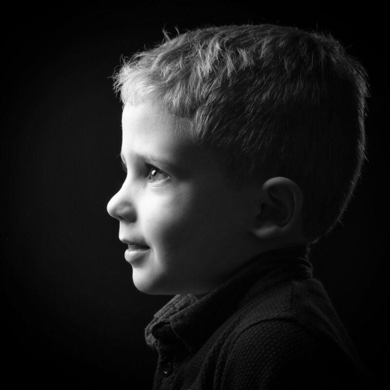 Portrait en studio en noir et blanc sur fond noir d'un petit garçon de profil pour Lorie Diaz