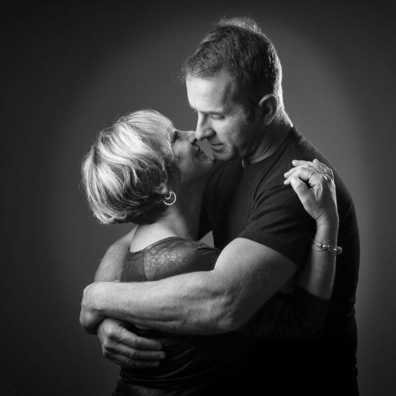 Portrait en noir et blanc en studio d'un couple qui s'embrasse sur fond gris pour Lorie Diaz photographe