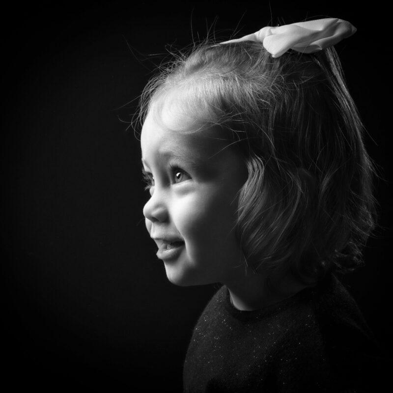 Portrait en studio en noir et blanc sur fond noir d'une petite fille de profil pour Lorie Diaz