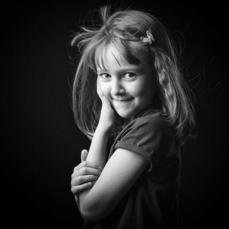 Portrait en studio en noir et blanc sur fond noir d'une petit fille pour Lorie Diaz