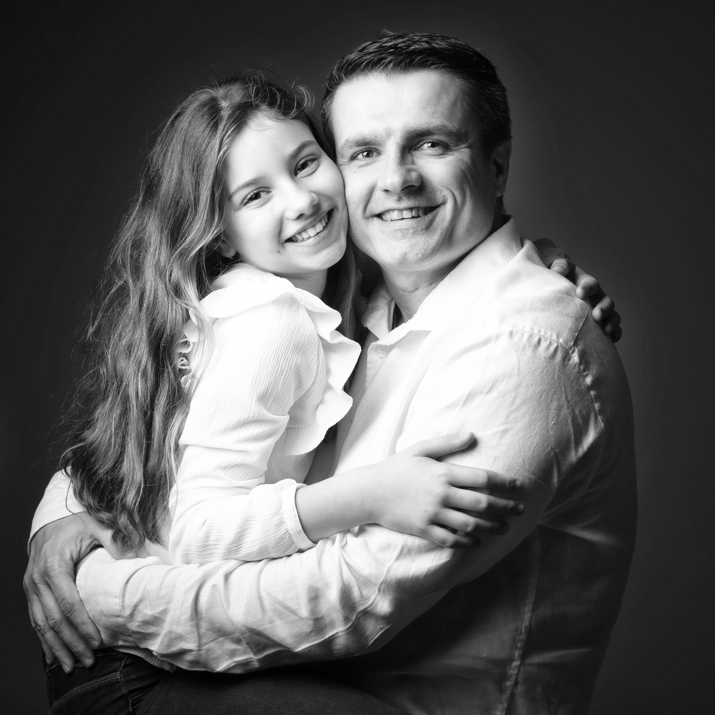 Portrait de famille d'une père et de sa fille dans ses bras en noir et blanc en studio sur fond noir pour Lorie Diaz photographe