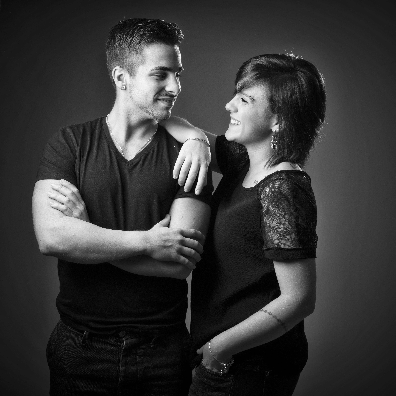 Portrait de famille d'un couple en noir et blanc sur fond gris pour Lorie Diaz photographe