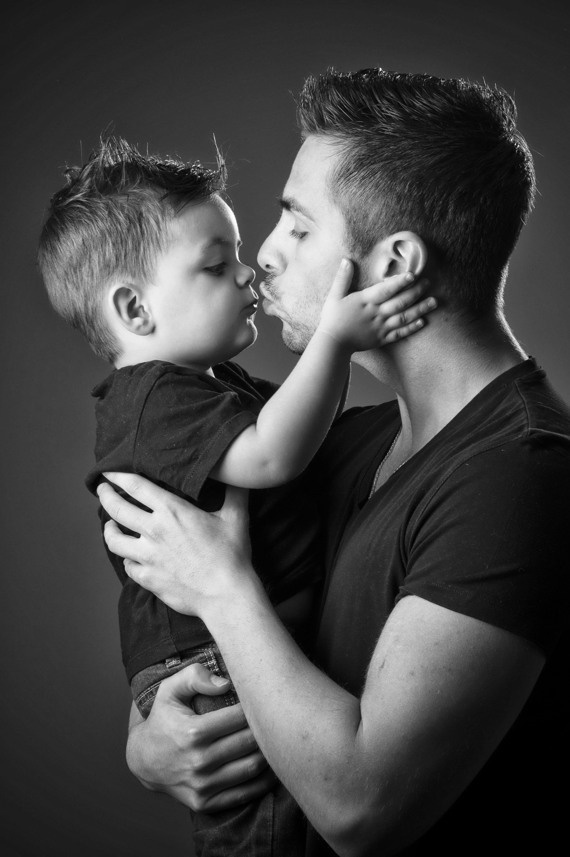 Portrait de famille en noir et blanc en studio sur fond gris d'un père avec son fils dans les bras pour Lorie Diaz photographe