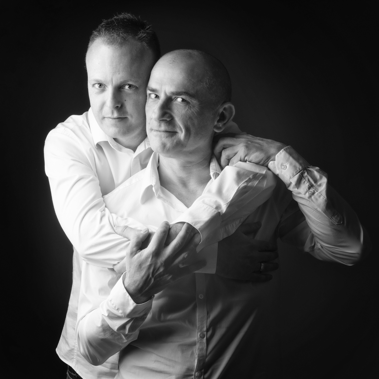 Portrait en noir et blanc en studio d'un couple d'hommes sur fond noir pour Lorie Diaz photographe