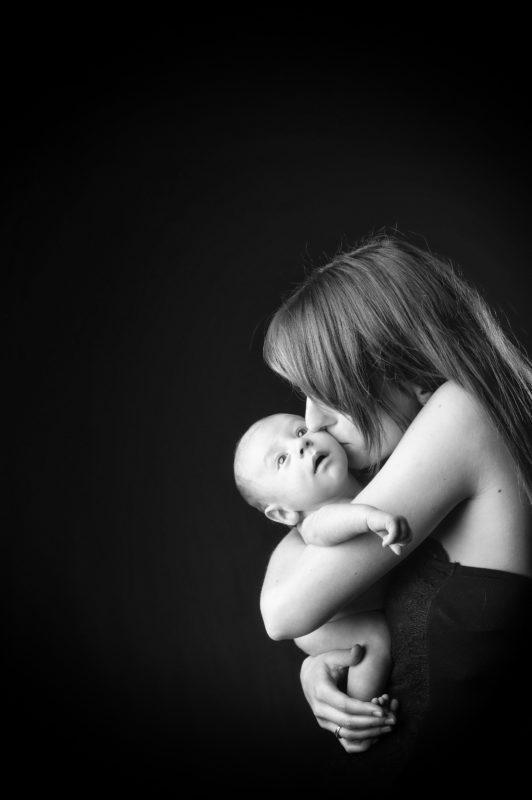 Portrait en noir et blanc en studio d'une jeune femme qui embrasse son bébé dans ses bras pour Lorie Diaz Photographe
