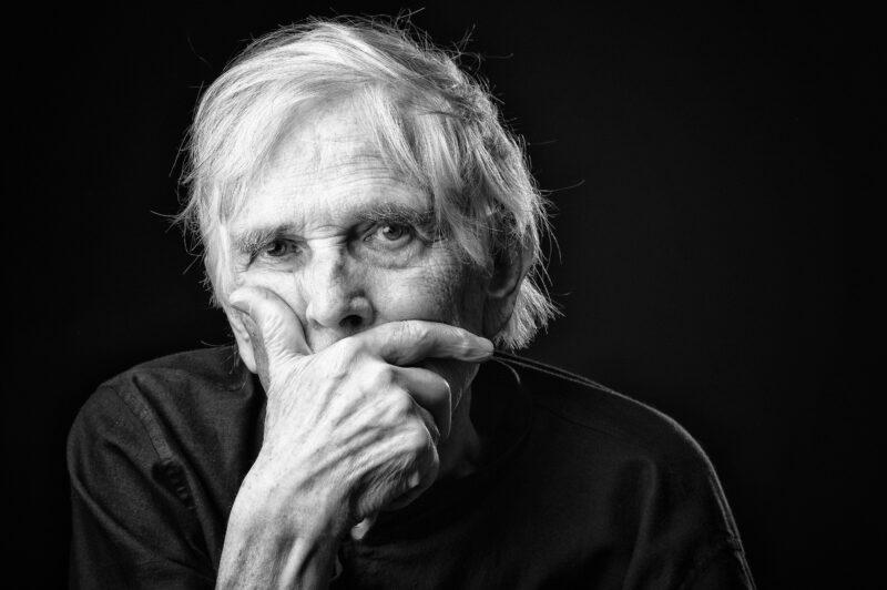 Portrait en studio en noir et blanc sur fond noir d'un homme âgé avec la main devant la bouche pour Lorie Diaz